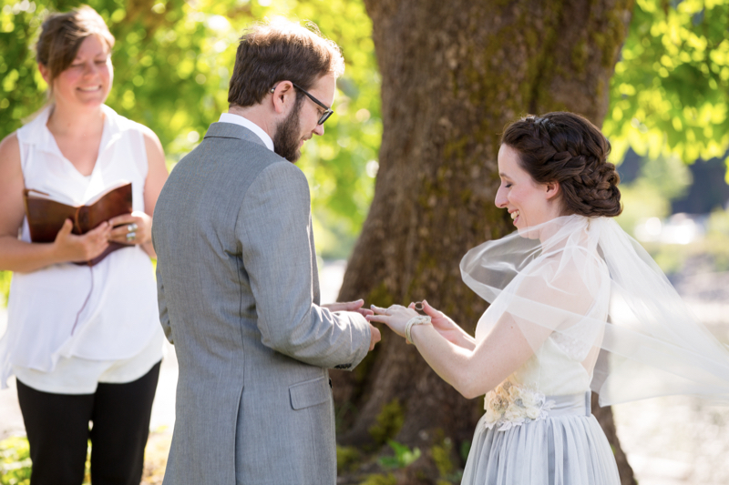 bride and groom putting on wedding rings